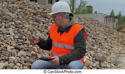 Construction inspector near the pile of crushed stone