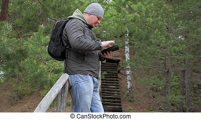 Hiker with tablet PC in forest