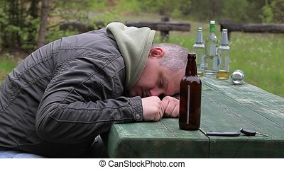 Drunk men with bottle of alcohol at outdoor
