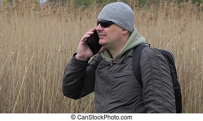 Hiker talking on cell phone near cane