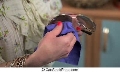 Woman with napkin cleaning Sunglasses