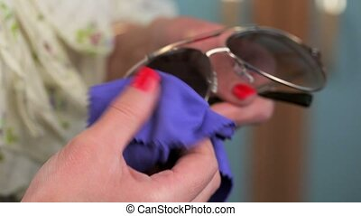 Woman cleaning Sunglasses