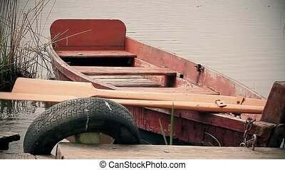 Old wooden fishing boat near lake