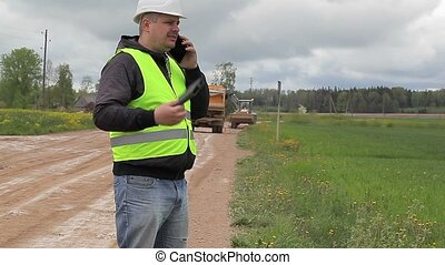 Engineer with cell phone in road repairs