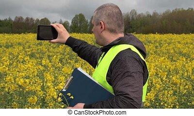 Farmer filmed with tablet PC yellow rape field