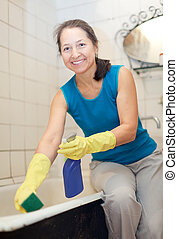 woman cleans bathroom with sponge and cleaner at her home