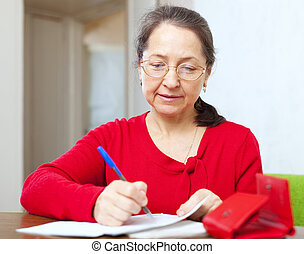 mature woman is calculated family budget - serious mature...
