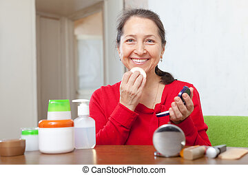 mature woman putting facepowder on face - Smiling mature...