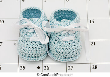 Baby Due Date - Blue baby booties on a calendar background,...