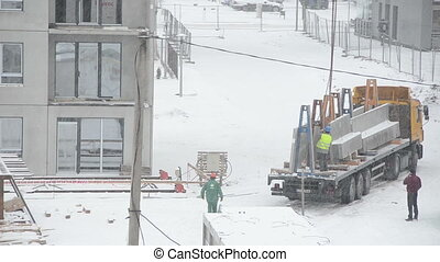 crane worker snow fall - Builders with crane work in...