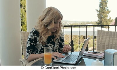 Attractive young woman working at a laptop in a cafe on the terrace