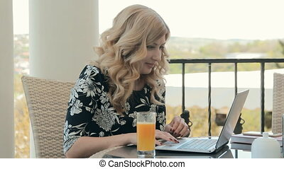 Attractive young woman typing on a laptop and drinking...
