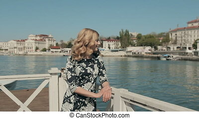 Charming young woman in dress standing on a wooden pier near the sea and smiling