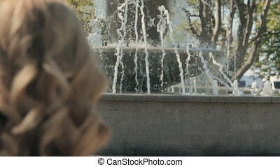 Woman with the curly hair looking at the fountain