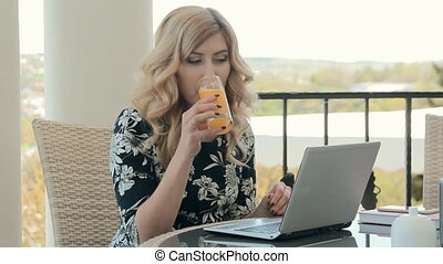Attractive young woman drinking orange juice in a restaurant...