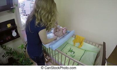 mother baby diapers - Mother changing her newborn baby girl...