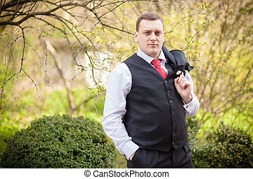 groom vest in greeen beautiful park in summer