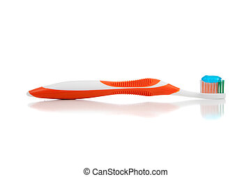 An orange toothbrush with paste on white