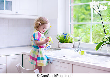 Little girl washing dishes - Child washing dishes. Kids wash...