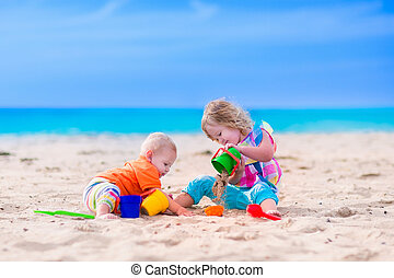 Kids building a sand castle on a beach - Kids play on a...