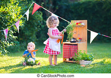 Kids playing with a toy kitchen in a summer garden - Kids...
