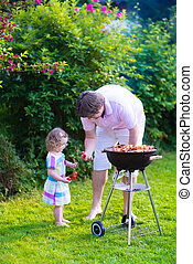 Father and daughter grilling meat - Father and child...