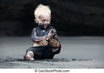 Portrait of dirty child on the black san beach - Funny...