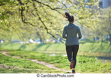 woman jogging in park at morning - young woman jogging in...