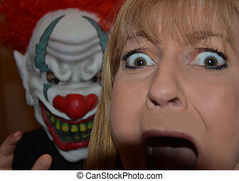 Fright Night clown of horror - woman being frightened by a...