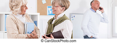Elder women talking - Elder women holding books and talking,...
