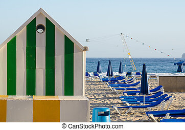 Beach hut and deckchairs on sunny Benidorm beach, Costa...