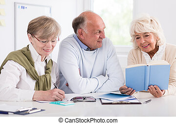 Happy retirees studying - Smiling happy retirees studying at...