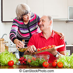 Smiling mature couple cooking together in home kitchen
