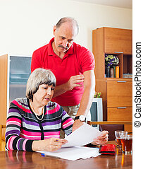 serious mature couple calculating family budget at home...