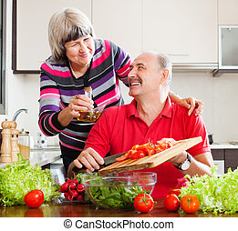happy elderly couple cooking with tomatoes - happy loving...