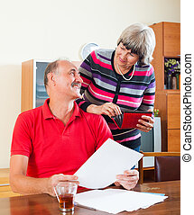 mature couple looking financial documents - Positive mature...