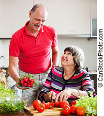 Senior man and mature woman cooking lunch - Senior man and...