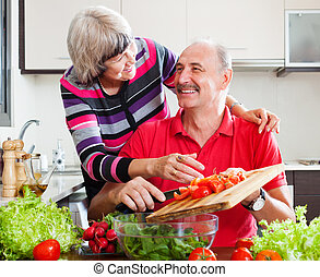 happy loving elderly couple in kitchen at home