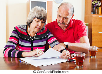 serious mature couple reading document - serious mature...