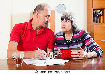pensive mature couple calculating family budget at home...