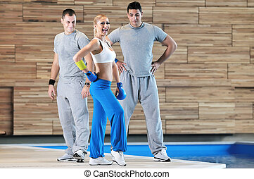 fitness group exercise - group of young adults exercise in...