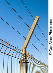 Security barbed wire fence against blue sky