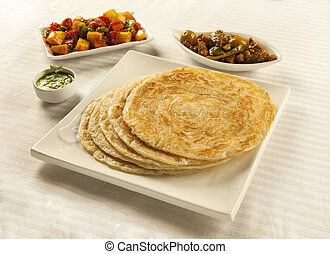 Paratha served with mixed vegetables, chutney and pickles