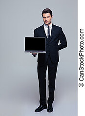 Businessman showing blank laptop screen - Full length...