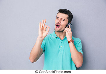 Happy young man talking on the phone and gesturing ok sign...