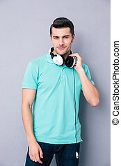 Casual man standing with headphones over gray background