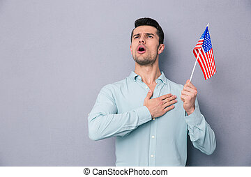 Patriotic young man holding US flag over gray background