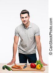 Man leaning on the table with vegetables isolated on a white...