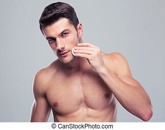 Man cleaning face skin with batting cotton pads - Handsome...