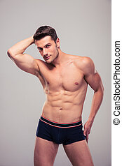 Portrait of a sexy muscular man posing over gray background....